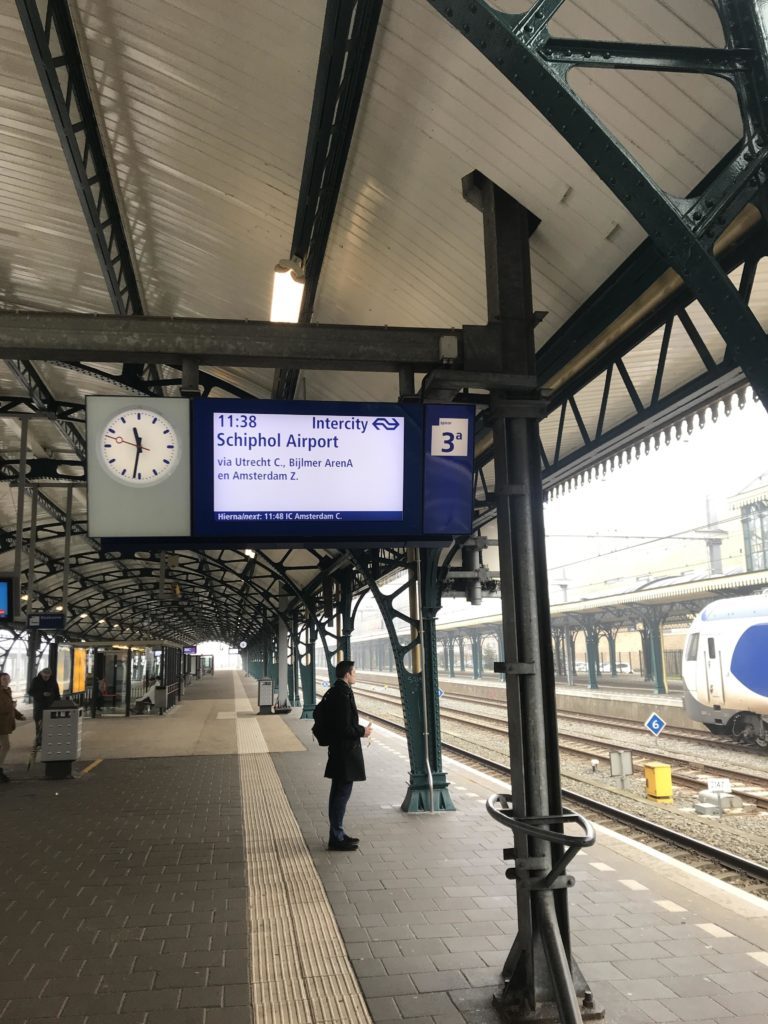 Picture of a man waiting for a train to Schiphol Airport on a platform at the train station in Den Bosch, The Netherlands